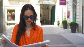 Молодая женщина с картой города в городе Путешествуйте туристская девушка с картой в вене outdoors во время праздников в Европе видеоматериал