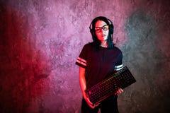 Молодая женщина с клавиатурой представляя перед стеной освещенной с красными неоновыми цветами Игры Gamer стоковое фото