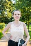 Молодая женщина с книгой идя в парк стоковое фото rf