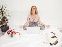 Молодая женщина с компьтер-книжкой в кровати Стоковая Фотография