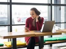 Молодая женщина с компьтер-книжкой и мобильным телефоном в кафе Стоковое Изображение