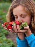 Молодая женщина с красными свежими клубниками в руках Стоковые Фотографии RF