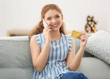 Молодая женщина с кредитной карточкой говоря на телефоне стоковые изображения rf