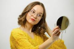 Молодая женщина с круглыми зрелищами смотрит в зеркале и исправляет ее изолированные волосы над белизной стоковое изображение