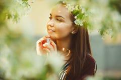 Молодая женщина с мечтательными стойками посреди blossoming дерева Стоковое Фото