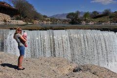 Молодая женщина с младенцем на водопаде Стоковое фото RF