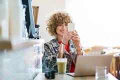 Молодая женщина с мобильным телефоном в кафе стоковое изображение rf