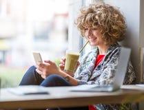 Молодая женщина с мобильным телефоном в кафе стоковые фотографии rf