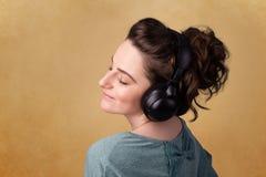 Молодая женщина с наушниками слушая к музыке с космосом экземпляра Стоковая Фотография RF