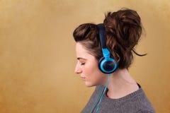 Молодая женщина с наушниками слушая к музыке с космосом экземпляра Стоковое фото RF