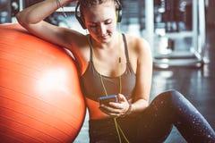 Молодая женщина с наушниками слушая к музыке после трудной разминки стоковое фото