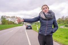 Молодая женщина с нервным расстройством автомобиля хочет путешествовать автостопом стоковые изображения
