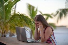 Молодая женщина с ноутбуком на пляже стоковое изображение rf