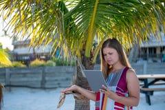 Молодая женщина с планшетом на пляже стоковые изображения rf