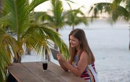 Молодая женщина с планшетом на пляже стоковые фотографии rf