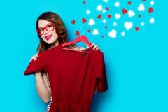 Молодая женщина с платьем на вешалке и абстрактных сердцах Стоковые Изображения RF