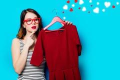Молодая женщина с платьем на вешалке и абстрактных сердцах Стоковая Фотография