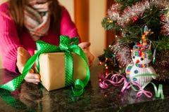 Молодая женщина с подарочной коробкой около рождественской елки, счастливый Новый Год Стоковое Изображение RF