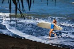 Молодая женщина с прогулкой surfboard на пляже отработанной формовочной смеси стоковое изображение rf