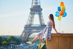 Молодая женщина с пуком воздушных шаров около Эйфелевой башни Стоковое Фото