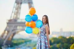 Молодая женщина с пуком воздушных шаров около Эйфелевой башни Стоковая Фотография
