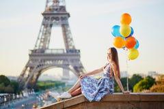 Молодая женщина с пуком воздушных шаров около Эйфелевой башни Стоковые Фотографии RF