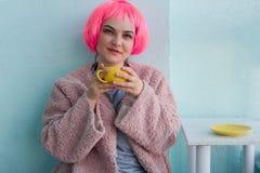 молодая женщина с розовыми волосами в розовой меховой шыбе сидя в кофейне и держа желтую кружку кофе стоковое фото