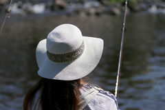 Молодая женщина с ростками и dungarees лета пока удящ Стоковое Фото