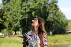 Молодая женщина с ростками и dungarees лета пока удящ Стоковое Изображение