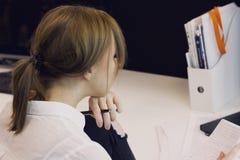Молодая женщина с ручкой в руке читая сочинительство в тетради Стоковое Изображение