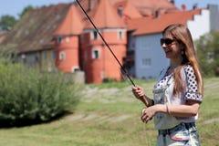 Молодая женщина с рыболовной удочкой на реке в Германии Стоковая Фотография