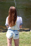 Молодая женщина с рыболовной удочкой на реке в Германии Стоковые Изображения RF