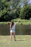 Молодая женщина с рыболовной удочкой на реке в Германии Стоковое фото RF