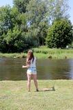 Молодая женщина с рыболовной удочкой на реке в Германии Стоковые Фотографии RF