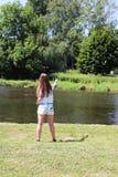 Молодая женщина с рыболовной удочкой на реке в Германии Стоковое Изображение RF
