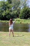 Молодая женщина с рыболовной удочкой на реке в Германии Стоковое Фото
