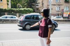 Молодая женщина с рюкзаком заминк-пешим на дороге стоковые фото