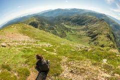 Молодая женщина с рюкзаком сидит на утесе в Mountain View Стоковое Изображение