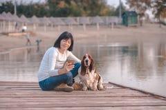 Молодая женщина с собакой используя умный телефон стоковое изображение rf