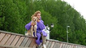 Молодая женщина с собакой на пляже рекой видеоматериал