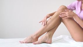 Молодая женщина с совершенным телом сидит с ровными шелковистыми ногами после депиляции Концепция депиляции, ровной кожи видеоматериал
