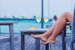 Молодая женщина с стеклом белого вина на вечере стоковые изображения