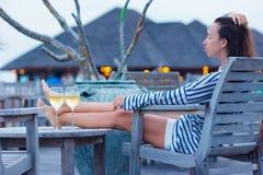 Молодая женщина с стеклом белого вина на вечере стоковое изображение