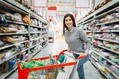 Молодая женщина с тележкой вполне товаров в супермаркете стоковая фотография