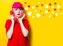 Молодая женщина с телефонной трубкой и абстрактными сердцами Стоковое Изображение
