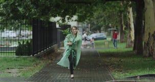 Молодая женщина с цветком идя на улицу на день дождя, счастливую слушая музыку от наушников сток-видео
