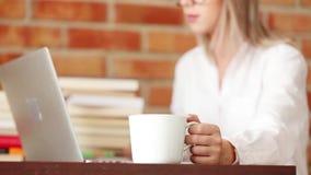 Молодая женщина с чашкой и портативным компьютером акции видеоматериалы