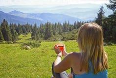 Молодая женщина с чашкой чаю, кофе, сидя на траве стоковые изображения rf