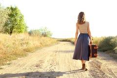 Молодая женщина с чемоданом идя вдоль дороги стоковое изображение rf