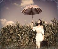 Молодая женщина с чемоданом и зонтиком Стоковые Изображения